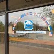 Les drapeaux d'une quinzaine d'États membres de l'organisation sont peints en demi-cercle sur la vitrine des bureaux.