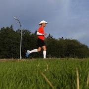 Dave Proctor vêtu d'un chandail rouge et portant un chapeau de cowboy courant aux abords d'une route.