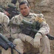 Lionel Desmond en uniforme militaire est assis, en Afghanistan, avec son fusil d'assaut sur ses genoux.