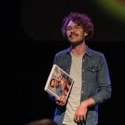 Un jeune homme aux cheveux frisés et portant des lunettes est éclairé sur une scène sombre.