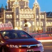 Une voiture rouge devant le Parlement législatif à Victoria.
