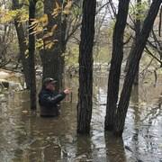 Un homme dans un champ inondé a de l'eau jusqu'à la taille.