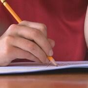 Un élève écrit dans un cahier d'exercices.