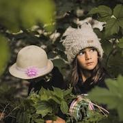 Deux enfants portant tuque et chapeau sont au milieu d'arbustes.