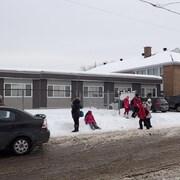 Des enfants jouent devant l'École Saint-Norbert, à Laval, où des classes modulaires ont été ajoutées en août 2017.