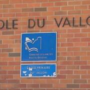 Une enseigne sur un mur de brique indiquant l'école du Vallon.