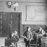 Un garçon se tient debout avec un bâton dans les mains, au milieu d'une classe.