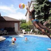 Une famille joue dans une piscine dans un quartier résidentiel.