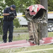Un policier prend une photo d'un débris d'avion.