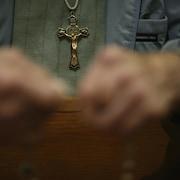 Un homme tient un chapelet entre ses mains durant la prière, à l'Église. Une croix pend à son cou.