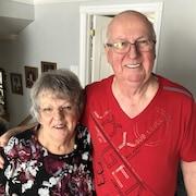 Photo d'un couple agé souriant à la caméra dans leur maison.