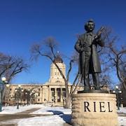 La statue de Louis Riel en avant-plan, la façade de l'Assemblée législative du Manitoba en arrière-plan.