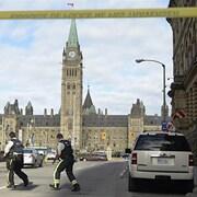 Trois policiers armés se dirigent vers le parlement.