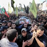 Des centaines d'hommes entourent un brancard sur lequel repose le corps de la victime.