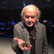 Georges Brossard tient une mygale dans sa main.