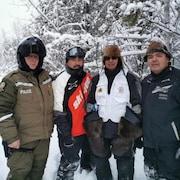 Quatre hommes, dont un policer, posent dans un sentier enneigé à côté d'une motoneige.