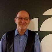 Gérard Jean se tient devant le logo de Radio-Canada.