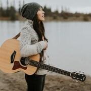 La chanteuse Ginalina tenant sa guitare près d'un lac en hiver.