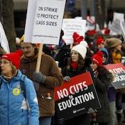 Des enseignants tiennent des affiches avec le message : « pas de coupes en éducation ».