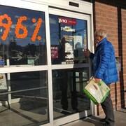 Un homme se bute à une porte fermée à une SAQ de Sherbrooke.