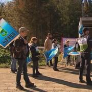 Des employés qui manifestent, drapeau syndical à la main.