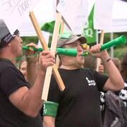 Des grévistes de la Sépaq soufflent dans des trompettes.