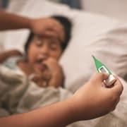 La mère d'une enfant couchée dans un lit prend sa température à l'aide d'un thermomètre.