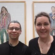 Sam et Marie-Ève sourient à la caméra, devant des tableaux montrant une femme et un homme aux formes diffuses.