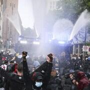 Des dizaines de manifestants se font asperger d'eau par deux camions de police.