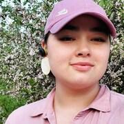 Hannah Tooktoo pose devant un arbre en fleur habillée d'un chemisier rose et d'une casquette rose.