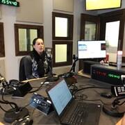 Annie Guay parle au micro dans le studio de radio.