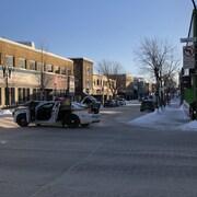 Un policier ouvre une porte d'une voiture de la Sûrté du québec, stationnée au milieu de l'intersection de la rue Gamble et l'avenue Principale.