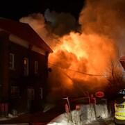 Un épais nuage de fumée mêlé de flammes se dégage d'un bâtiment.