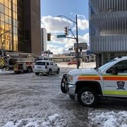 Un camion de pompiers et une ambulance sont sur scène d'intervention lors d'un incendie en ville. Il y a de la neige au sol