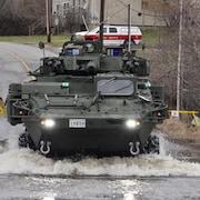 Un véhicule blindé circule sur une route inondée.