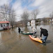 Trois résidents marchent en poussant un canot et un kayak vers une petite maison entourée d'eau.