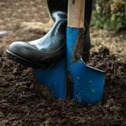 Un pied en botte pousse sur une pelle enfoncée dans la terre.
