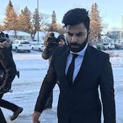 Jaskirat Singh Sidhu en costume marche en direction de l'entrée de la cour, à côté de lui des journalistes avec des caméras.