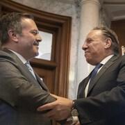 Jason Kenney et François Legault, tous les deux souriant, se serrant la main.
