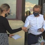 Jean Boulet donne des masques à deux femmes.