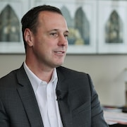 Dans son bureau, Jean-François Roberge écoute, décontracté, une question du journaliste de Radio-Canada. Des dossiers sont étalés sur son bureau derrière lui.