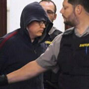 Jeffrey Paul Delisle escorté par des policiers au tribunal.