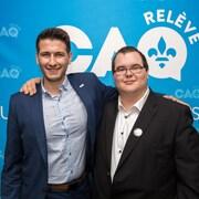 Deux hommes sourient à la caméra devant des logos de la relève de la CAQ.