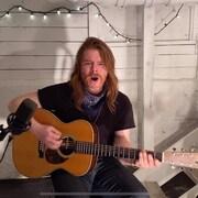 Un homme assis sur une chaise joue de la guitare et chante.