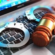 Sur un clavier d'ordinateur reposent des menottes ainsi qu'un maillet représentant la justice.