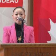 La candidate du Parti libéral Karen Wang donne un discours debout devant un microphone.