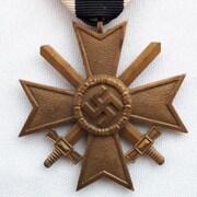 À gauche, une croix gamée sur une médaille et à droite, un canif avec une gravure d'un homme dans un habit du KKK.