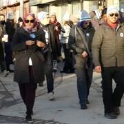 Des hommes et des femmes marchent sur un trottoir.
