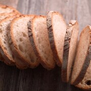 Des tranches de pain alignées sur une table en bois.