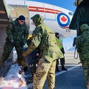 Des troupes des Forces armées canadiennes montent dans un avion.